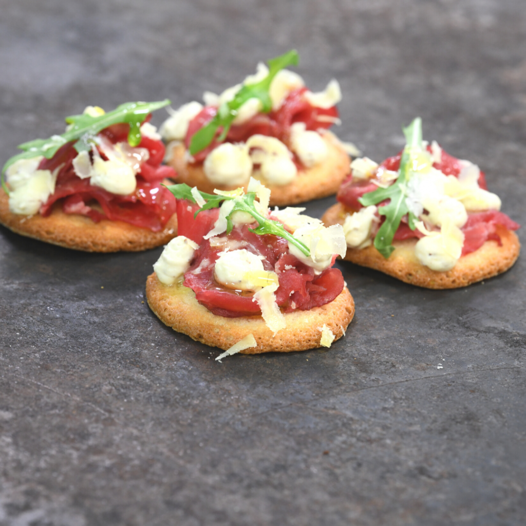 Teula biscuits combined with beef carpaccio, mustard foam, comté cheese and arugula
